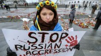 epa04583471 An Ukrainian woman holds a poster reading: 'Stop Russian aggression' during a mourning ceremony for people who died during a shelling in the eastern Ukrainian city of Mariupol, on the Independence Square in Kiev, Ukraine, 25 January 2015. Pro-Russian rebel forces in eastern Ukraine announced they would begin a large-scale attack of the eastern port city of Mariupol, but stopped short of taking responsibility for a shelling on 24 January in which at least 29 civilians died and about 100 were injured. The Organization for Security and Co-operation in Europe (OSCE) concluded the attack was launched from an area of eastern Ukraine controlled by pro-Russian separatists. An examination of a crater showed that the rockets were fired from the east and north-east from separatist areas, the OSCE said.  EPA/SERGEY DOLZHENKO